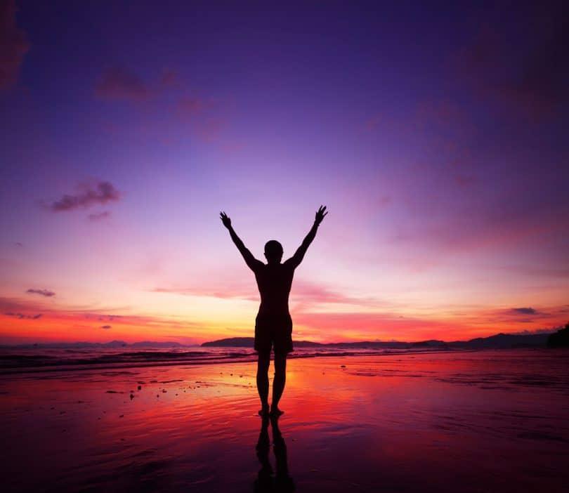 Silhueta de pessoa em pé na praia, andando na beira mar, com os braços para cima. Ao fundo o céu esta arroxeado/ avermelhado com o pôr do sol.
