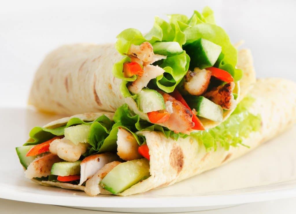 Dois wraps de grão de bico, recheado com vegetais e saladas, em um prato branco.
