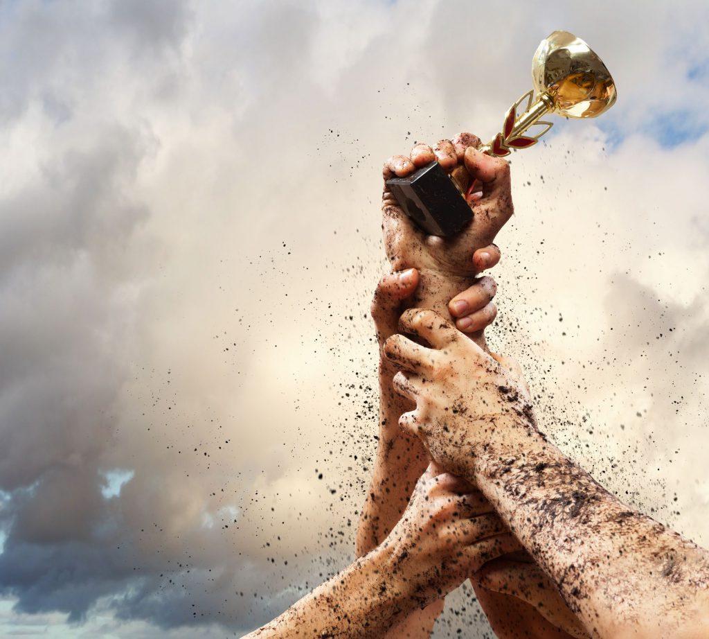 Mão de diversas pessoas lutando para segurar um troféu com uma pequena taça de ouro