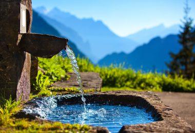 Fonte de água com paisagem de montanhas ao fundo.