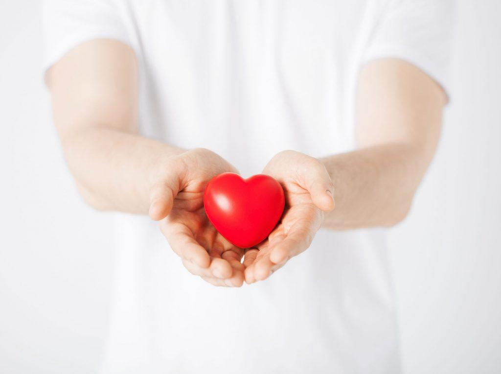 Close nas mãos de um homem segurado um coração vermelho