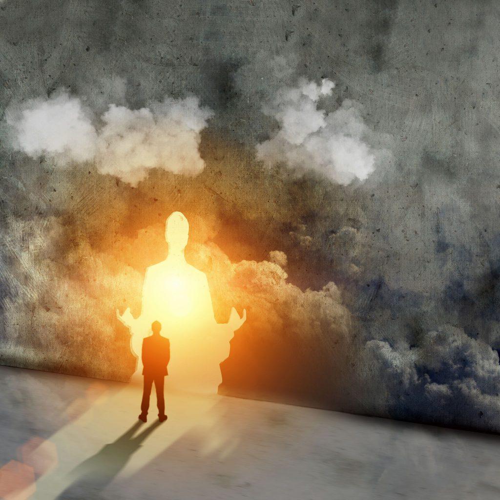 Contato com o Eu Superior: Silhueta de homem em uma sala cinza, encarando uma porta de saída iluminada com o formato de uma pessoa sentada meditando.