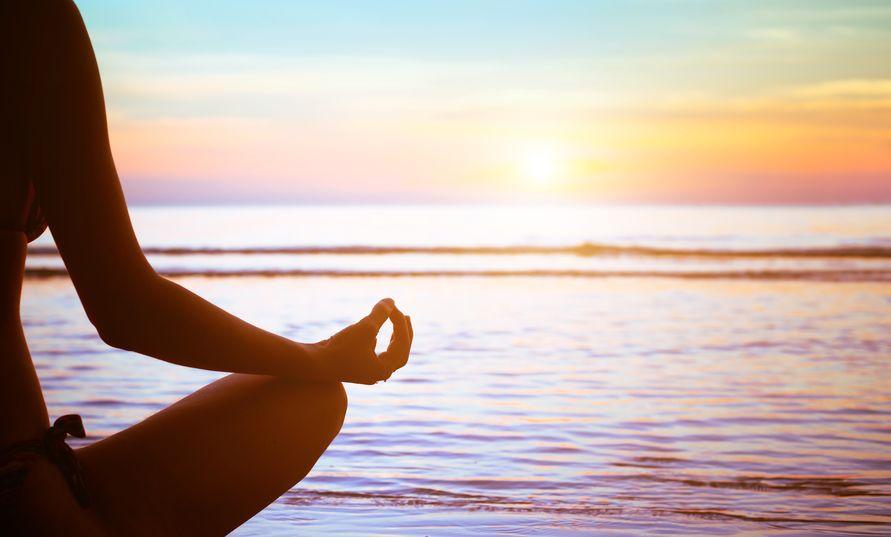 Silhueta de uma mulher meditando frente ao mar e ao nascer do Sol