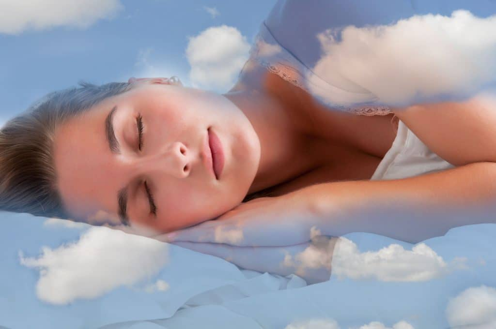 Mulher branca dormindo, deitada com a cabeça em cima das mãos, em uma cama branca com estampas do céu azul com nuvens.