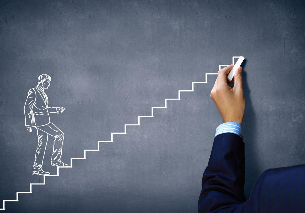 mão de pessoa desenhando com giz branco, em um quadro negro, uma pessoa subindo os degraus de uma escada