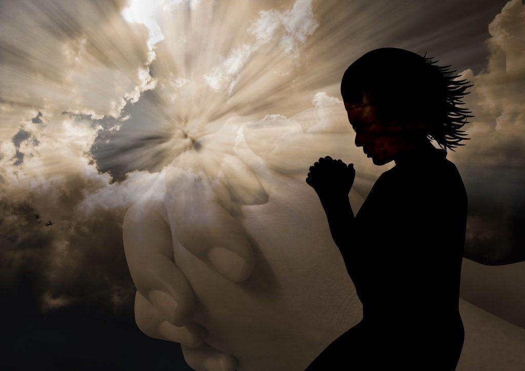 Mulher orando com as mãos juntas e de fundo uma sombra de um par de mãos juntas. Céu de fundo.