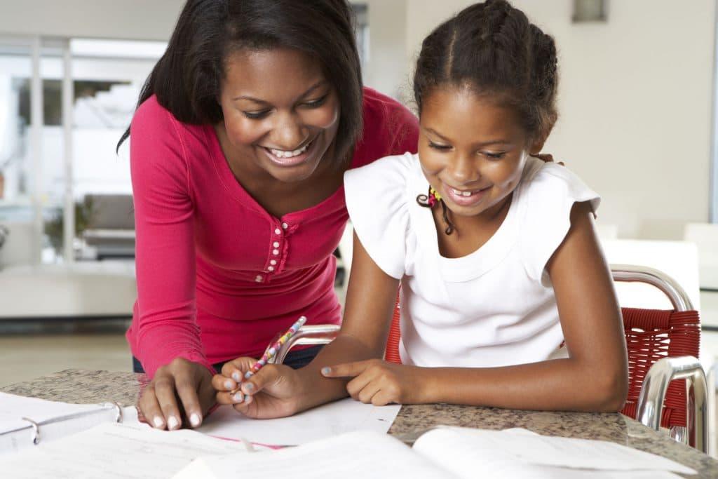 Mãe ajudando filha na lição de casa.