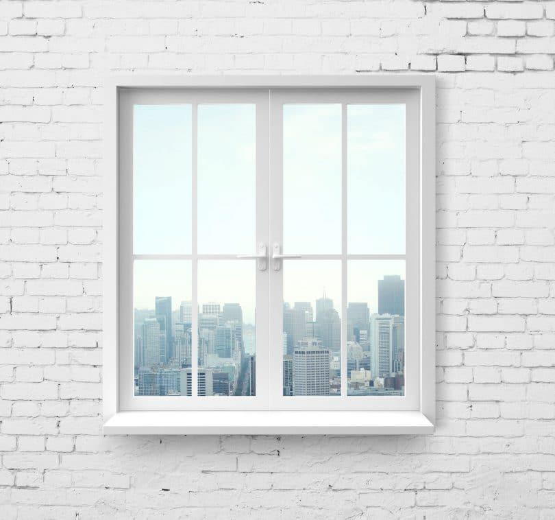 Foto de janela branca, em uma parede de tijolos branca, com vista para a cidade.
