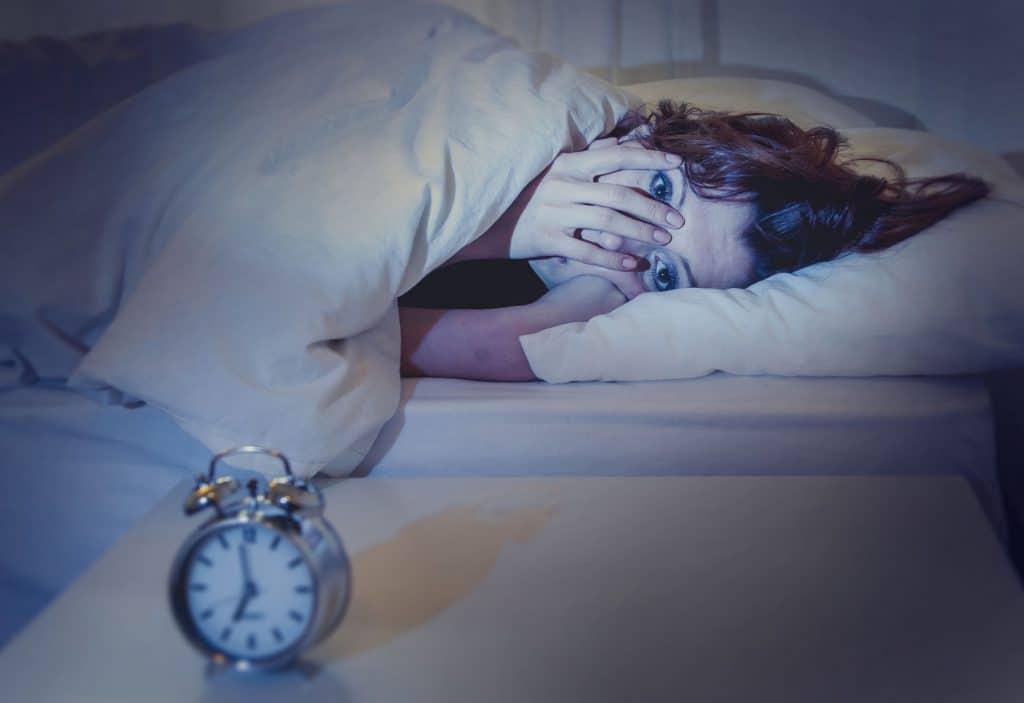 Mulher deitada em cama branca, com a mão no rosto e expressão de preocupação. Ao lado da cama há uma mesinha branca com um despertador prata em cima. Representação da insônia.