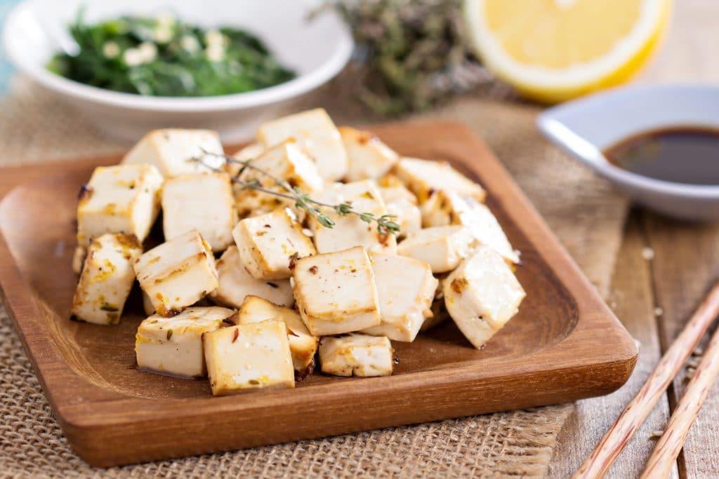 Tábua de madeira com diversos pedaços de tofu.
