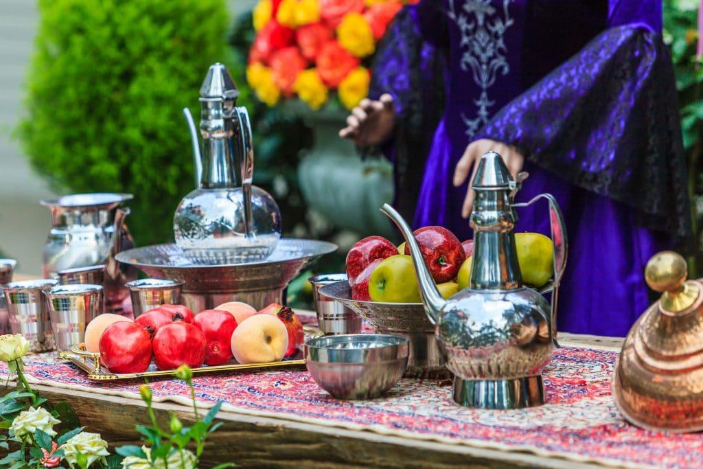 Foto de mesa de banquete medieval com diversas peças de prata e comidas.