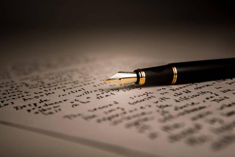 Caneta tinteiro preta e dourada colocada em cima de uma página de livro.