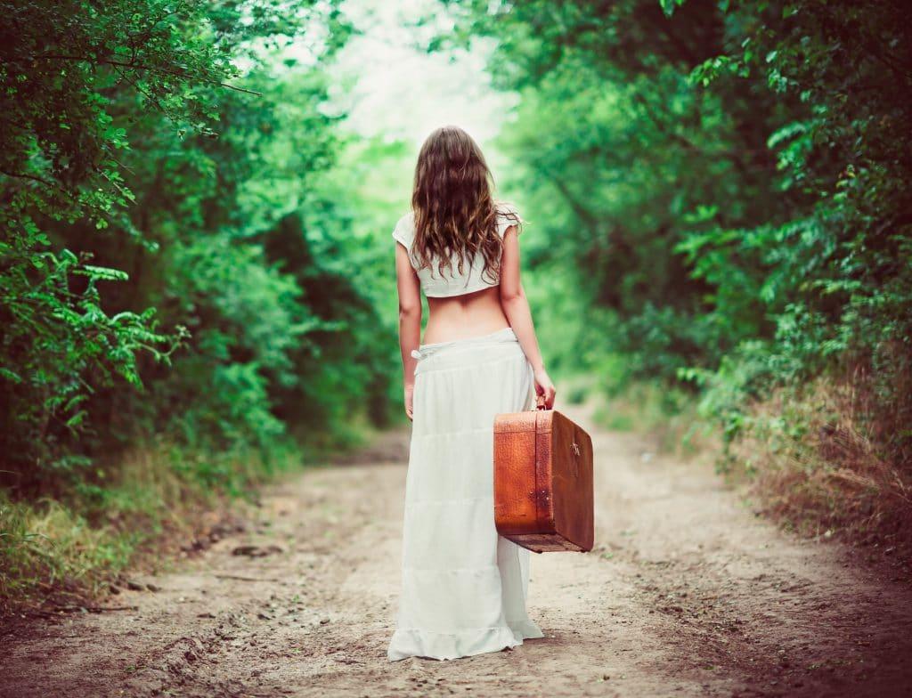 Mulher vestida de branco segurando uma mala de couro andando em caminho na floresta.
