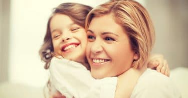 mãe e filho abraçados e sorrindo