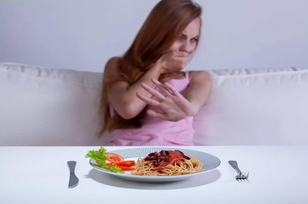 mulher sentada em mesa branca, recusando um prato de comida com macarrão e salada.