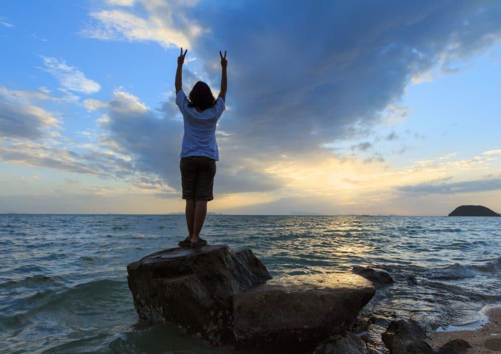 Mulher com as mãos levantadas em pedra na praia.