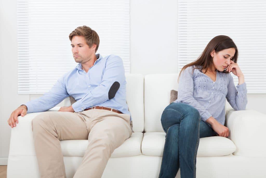 Casal de homem e mulher sentados em um sofá branco, ambos em silêncio e olhando para lados opostos.