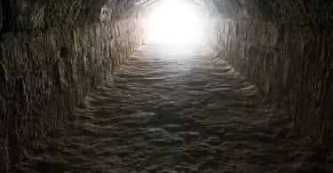 Fundo de poço escuro, com uma luz brilhando na saída do topo.