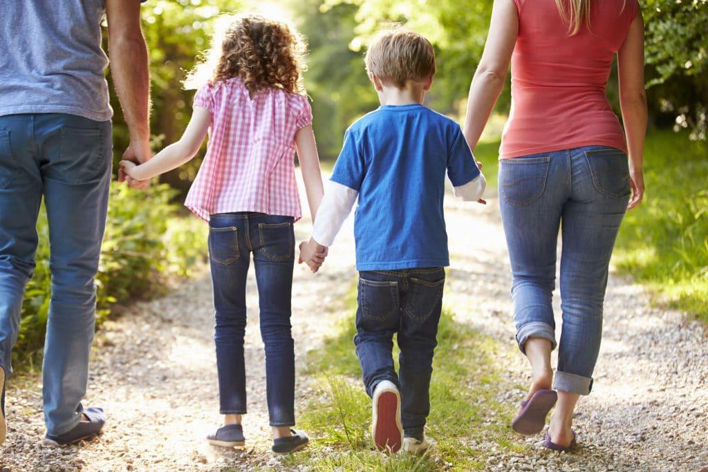 Família de mãos dadas andando. Fotografia de costas.