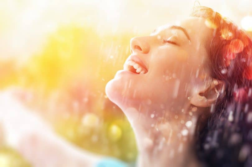 Mulher feliz, sorridente, tomando chuva no rosto.