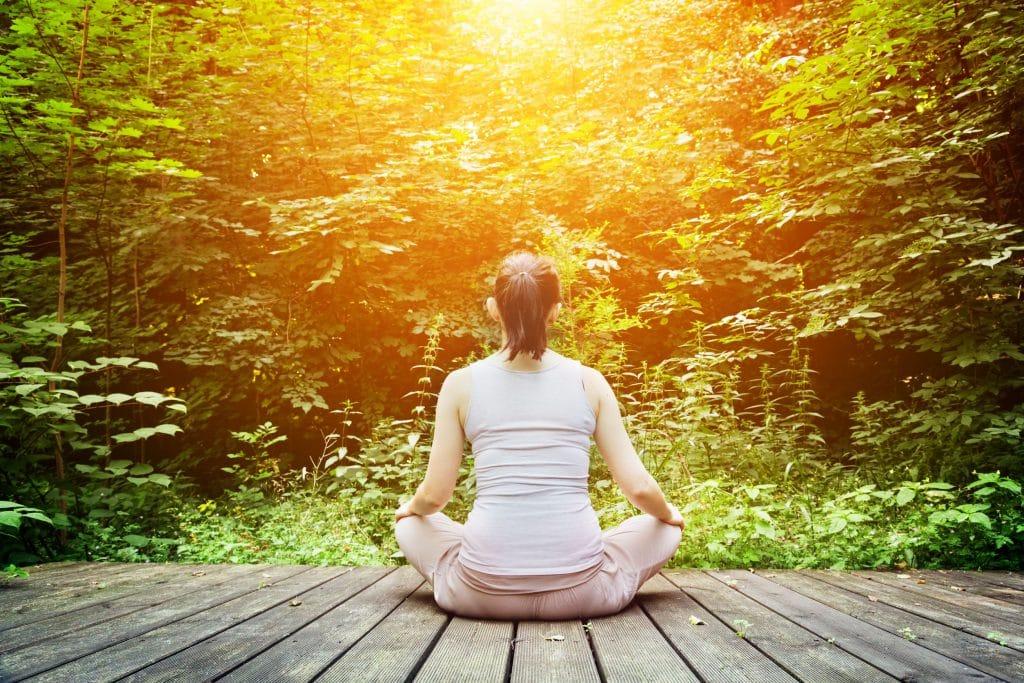 Mulher sentada com as pernas cruzadas em um pier de madeira, no meio da floresta, observando as árvores.