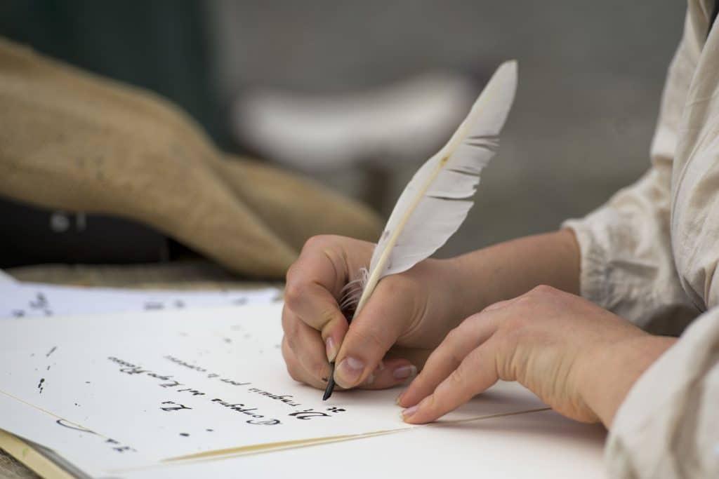 Pessoa escrevendo em papel branco com uma pena e tinta.