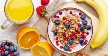 Mesa de café da manhã com uma tigela de frutas, frutas frescas cortadas e um copo de suco de laranja.