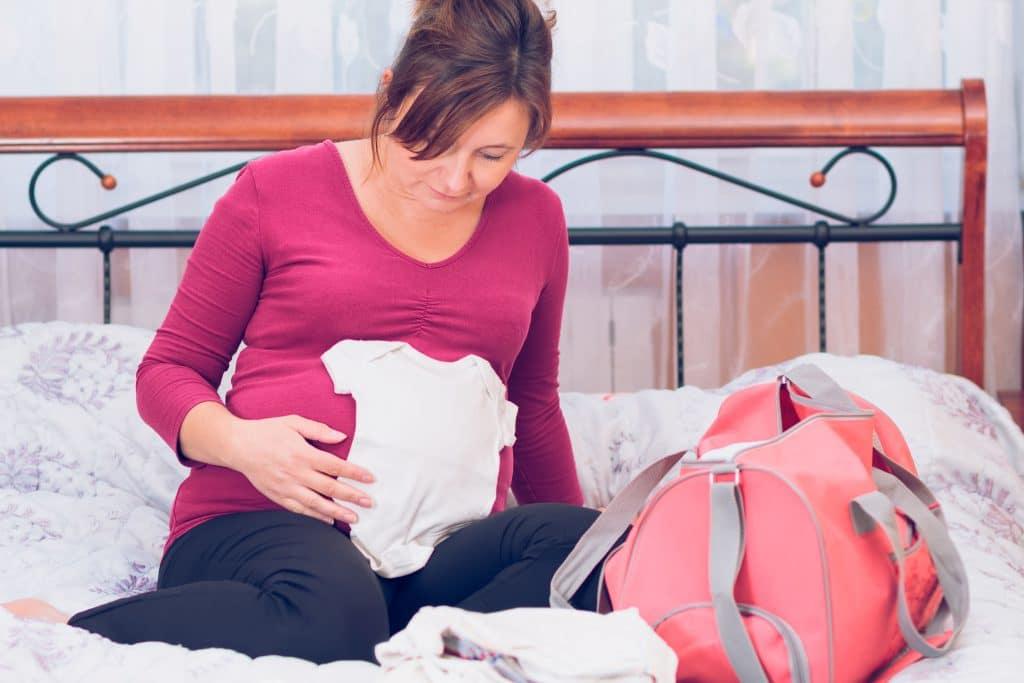 Mulher grávida, sentada em uma cama de casal, mexendo em roupas de bebe.