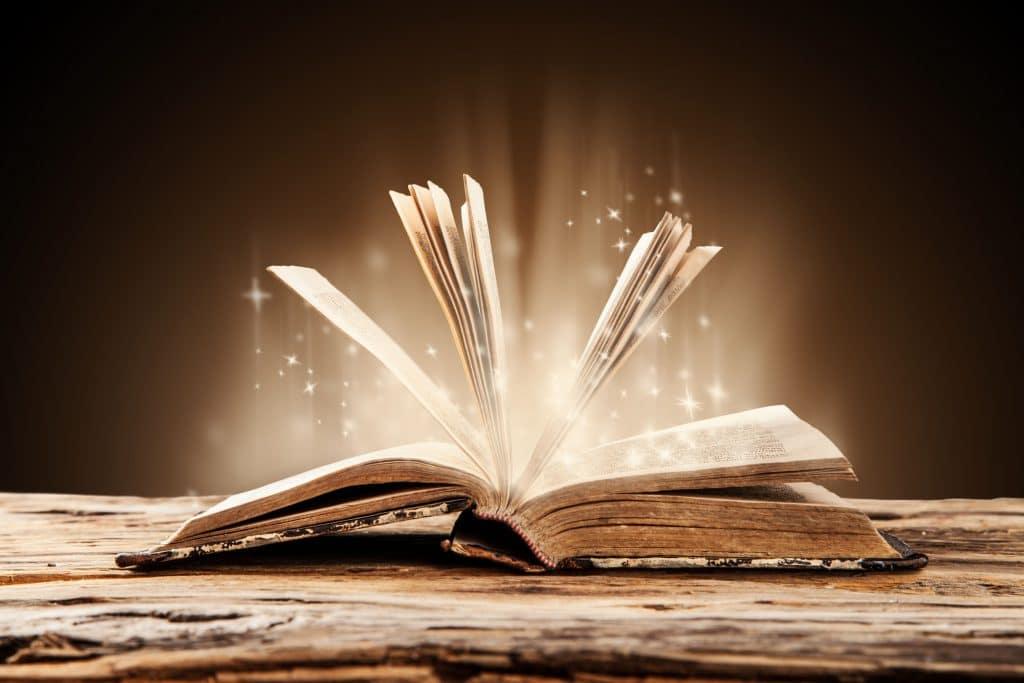 Livro aberto com luz saindo de dentro dele.