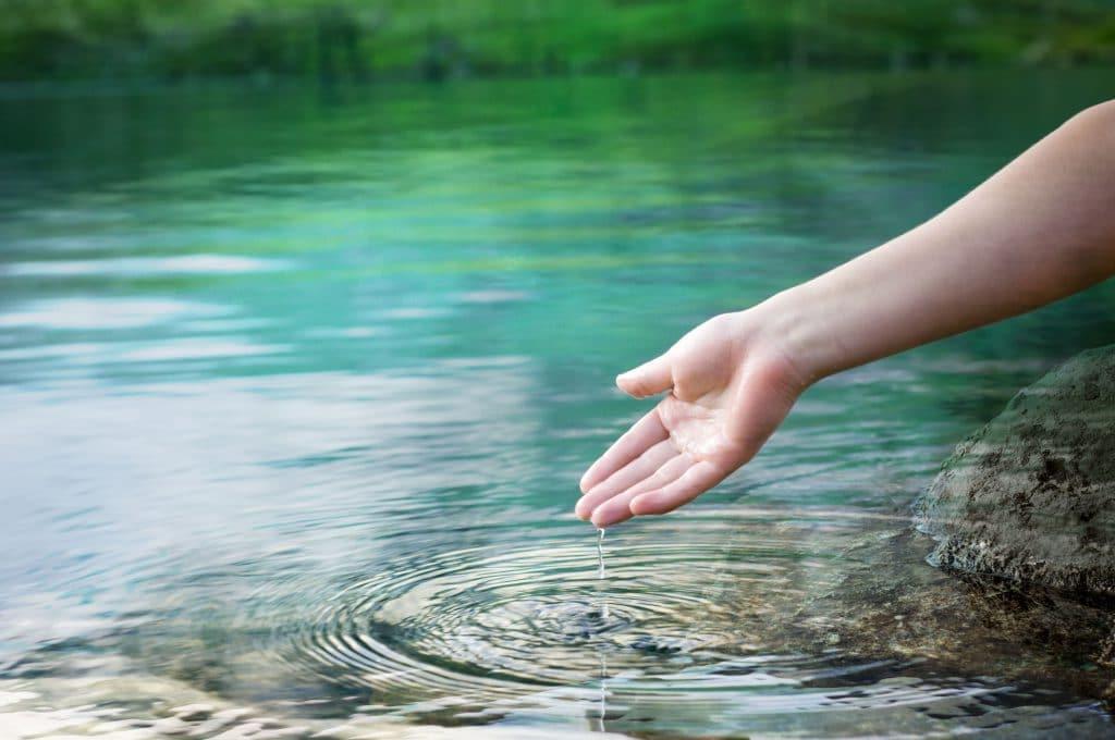 Mulher tirando a mão de um lago.