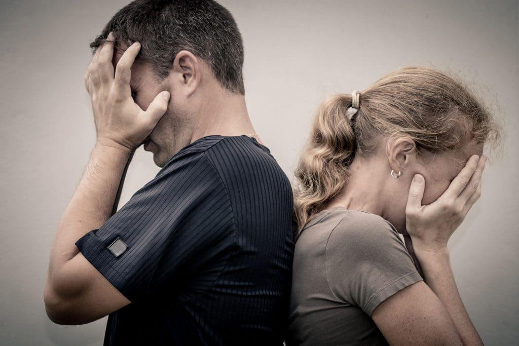 Homem e mulher, um de costas para o outro, ambos cobrindo o rosto com as mãos.