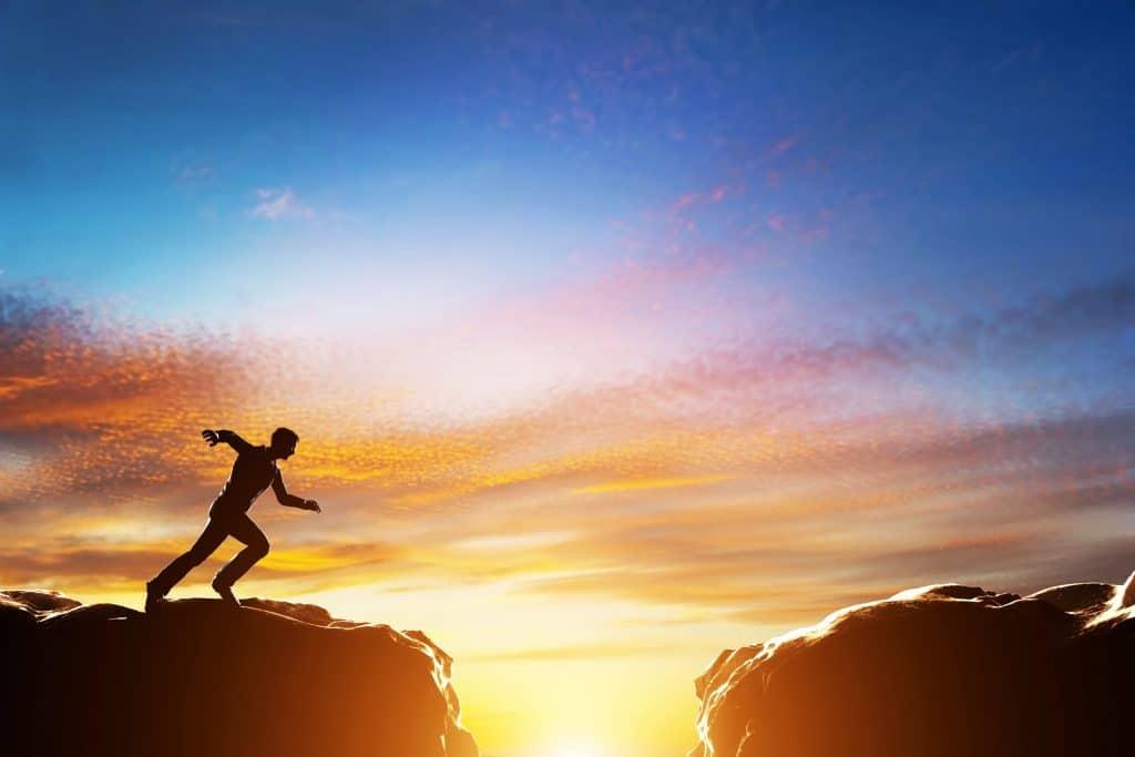 Homem correndo rápido para saltar sobre o precipício entre duas montanhas.