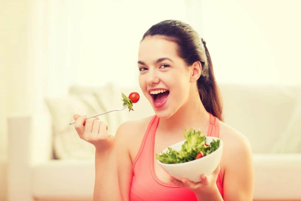 Mulher comendo salada e sorrindo para câmera.