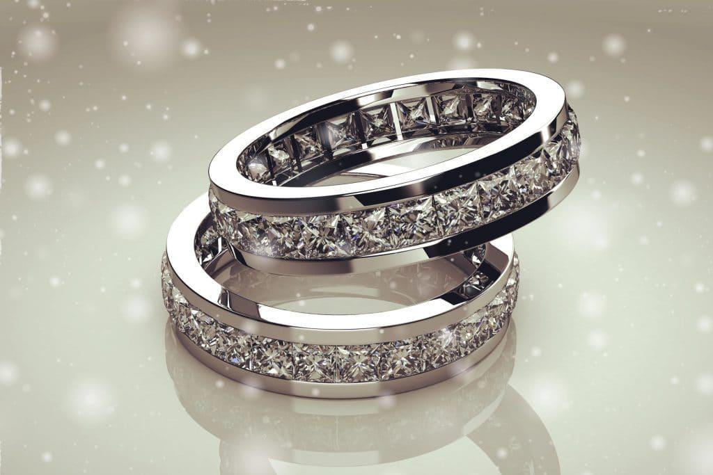 Dois anéis de prata, cravados em diamante, colocados em uma mesa branca brilhosa.
