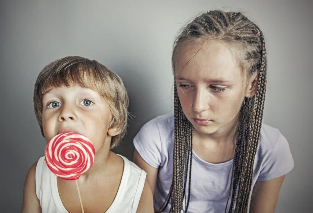 Irmã com ciúmes do irmão que come pirulito.
