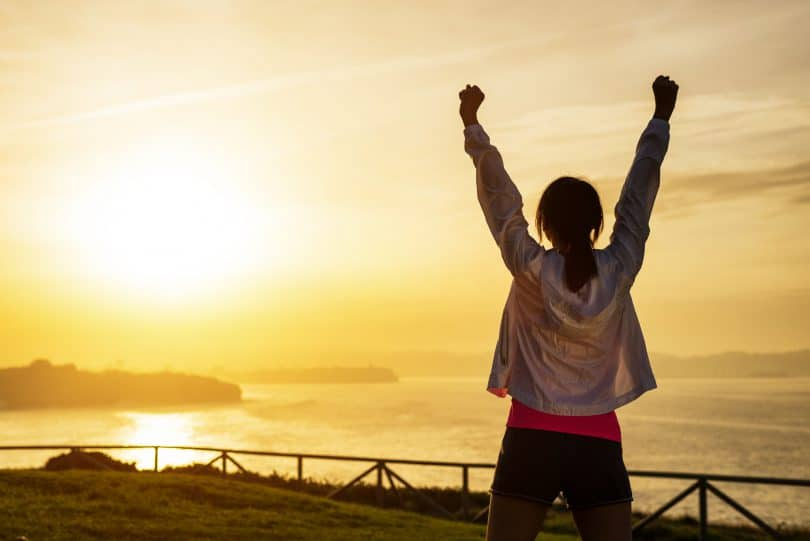 Mulher comemorando com os braços levantados olhando o pôr do sol.