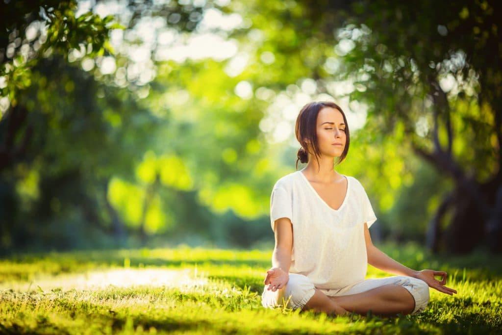 Mulher branca, vestida de branco, sentada na floresta, com as pernas cruzadas, meditando.