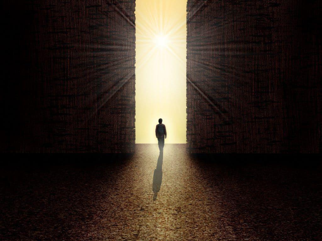 Silhueta de pessoa caminhando em uma sala escura, em direção à uma porta de saída de luz.