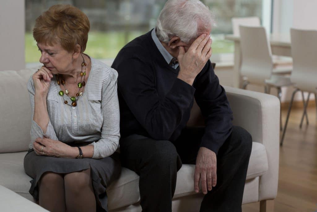 Casal de idosos sentados em silêncio, um de costas pro outro, no sofá de uma sala.