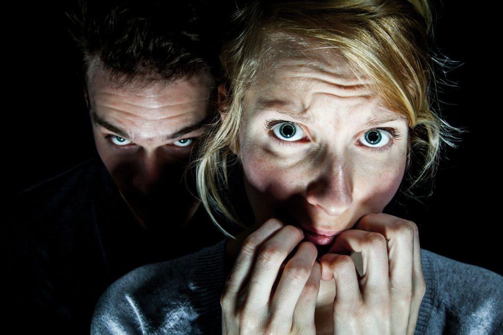 Mulher branca, assustada, roendo as unhas, com um homem observando-a por trás.