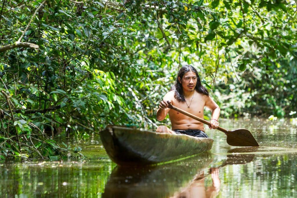 Índio remando no rio Amazonas.