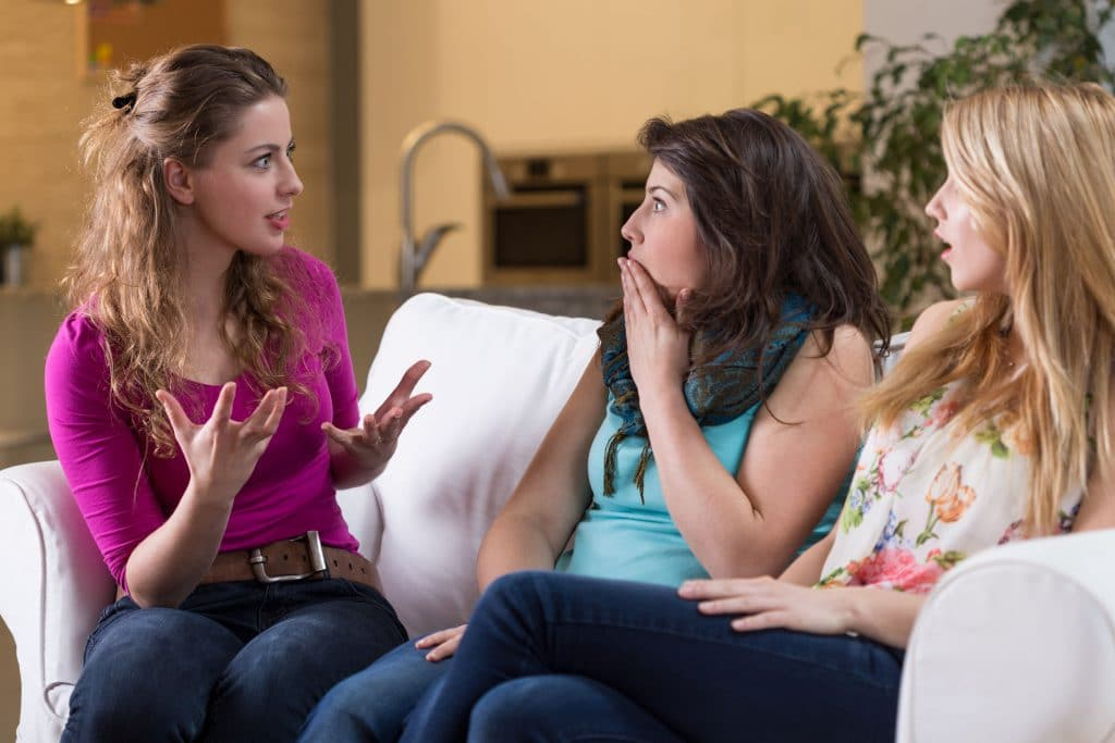 Mulheres conversando sentadas em sofá.