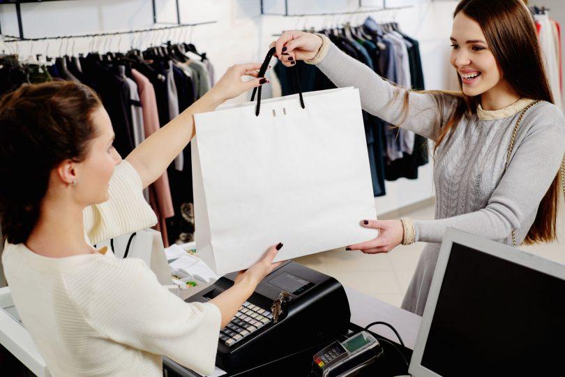 Consumidora comprando algo empacotado em sacola branca,