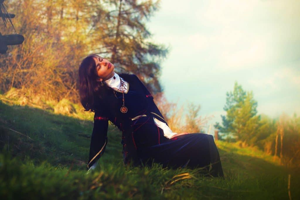 Mulher branca, próxima dos 50 anos, sentada na grama de um parque, tomando sol.