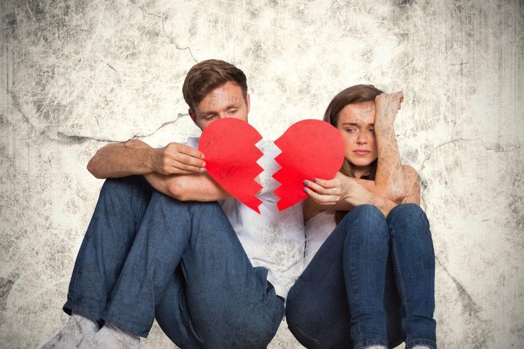 Casal chorando sentado lado a lado, cada um segurando a metade de um coração partido.