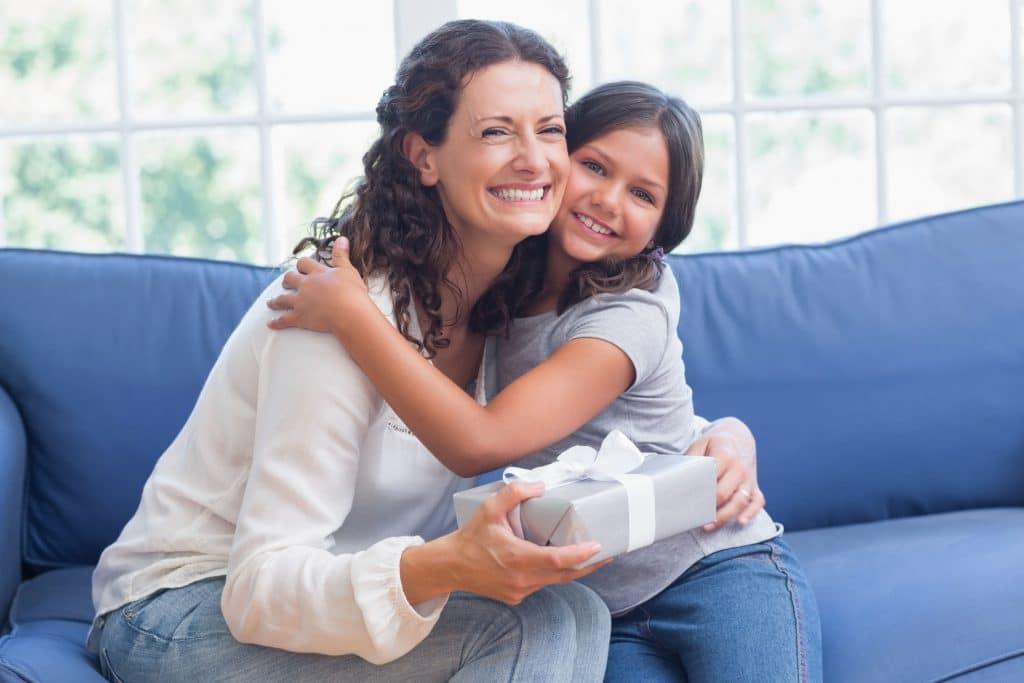 Mãe e filha criança sorridentes sentadas ambas em um grande sofá azul.