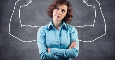 Mulher com os braços cruzados e camisa azul. Fundo de lousa preta com giz.
