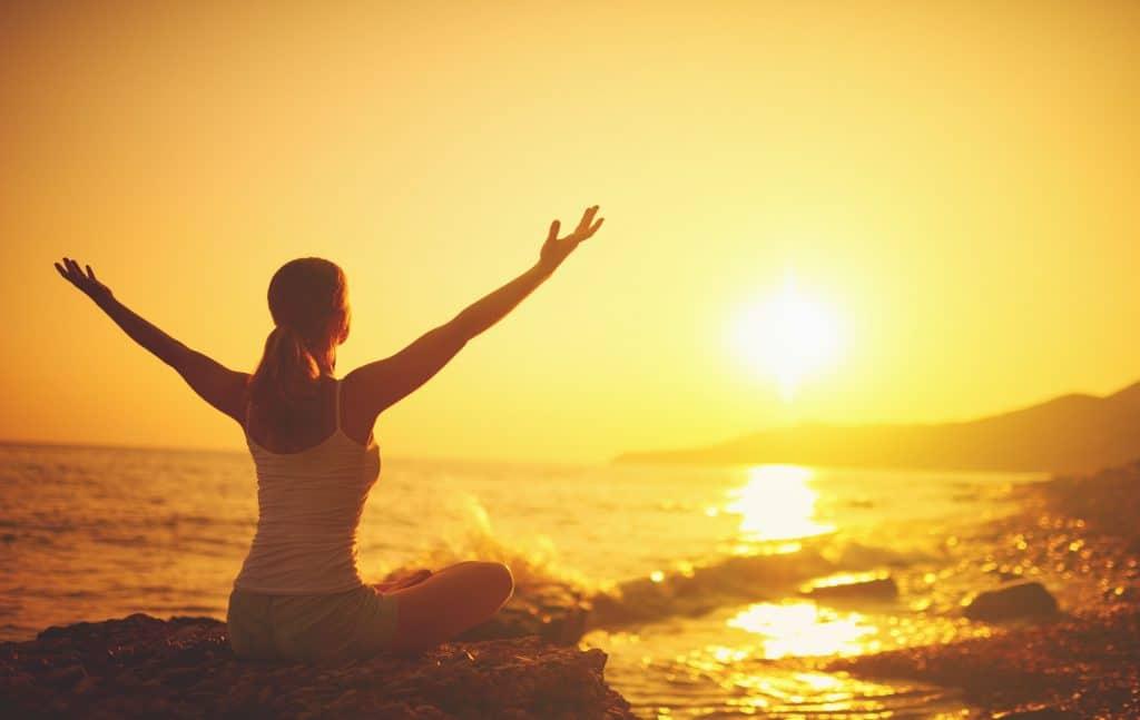Mulher branca, sentada com as pernas cruzadas, em posição de meditação, em cima de uma pedra, com os braços para cima, observando o sol.