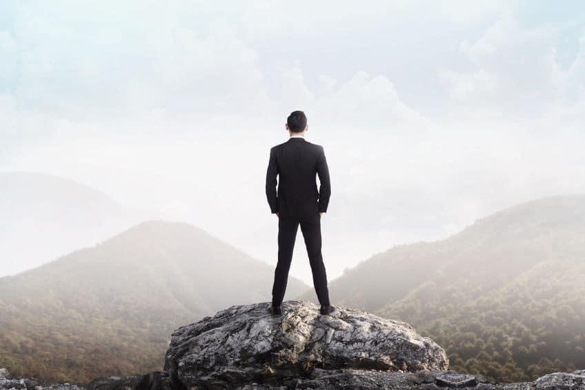 Homem de pé em uma montanha olhando para o horizonte