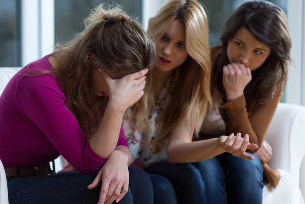 Menina chorando para as amigas enquanto elas aconselham.